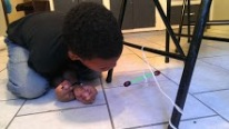 Isaiah prepares the balancing grapes to learn how water repells both sides of magnets!